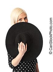 Attractive woman hiding behind hat
