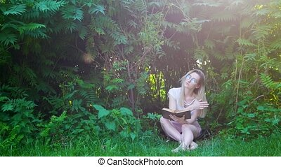 Attractive woman hipster sitting under a bushes and reading a book at sunset