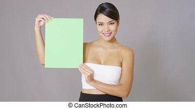 Attractive woman holding a blank green sign