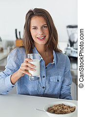 Attractive woman holding a glass of milk