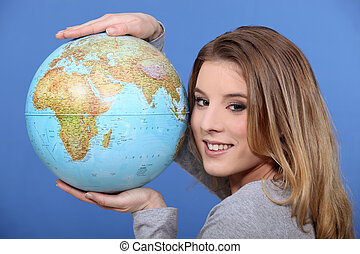 Attractive woman holding a globe