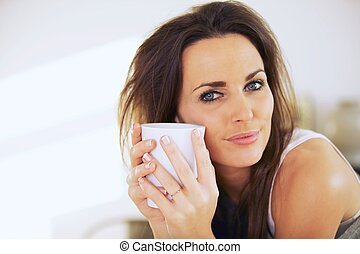 Attractive Woman Holding a Mug Close to Her Face