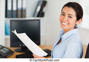 Attractive woman holding a sheet of paper and posing while sitting at the office
