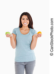 Attractive woman holding an apple and an orange