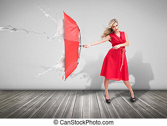Attractive woman holding an umbrella in an empty room to ...