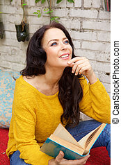 Attractive woman holding book and smiling