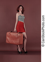 Attractive woman holding on a vintage suitcase