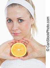 Attractive woman holding slice of orange