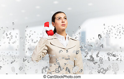 Attractive woman holding vintage red phone