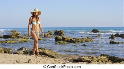 Attractive woman in a bikini walking on a beach