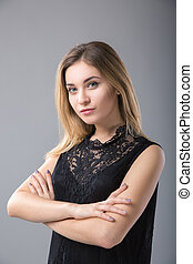 Attractive woman in a black dress on a background of a gray wall.