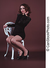 Attractive woman in a black dress sitting on a chair