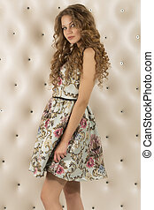 Attractive woman in a dress with curly hair