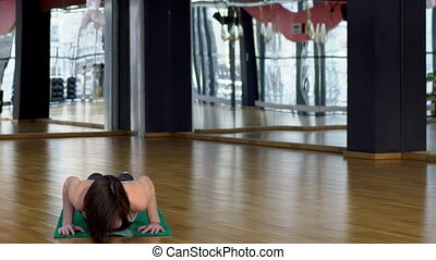 Attractive woman in a gym on a mate doing yoga exercises.