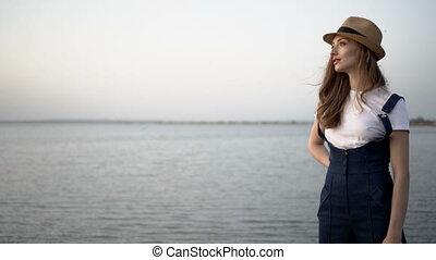 Attractive woman in a hat. Sunset