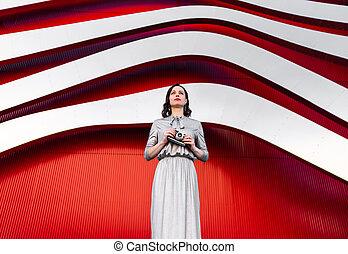 Attractive woman in a silver dress with a retro camera