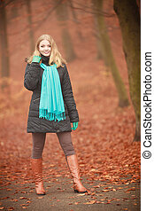 Attractive woman in autumnal park.