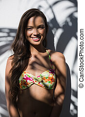 Attractive woman in bikini leaning against a wall