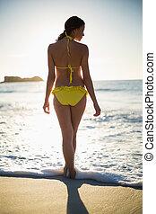 Attractive woman in bikini standing back to camera