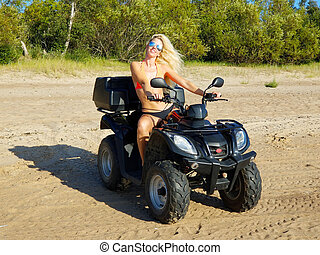 attractive woman in bikini with long blonde hair is sitting on the quad bike, sunny day.