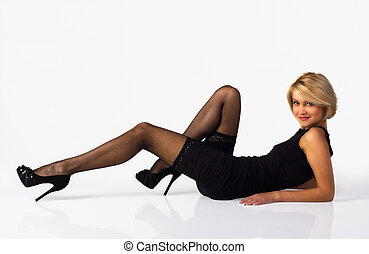 attractive woman in black dress posing lying on the floor
