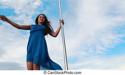 Attractive woman in blue dress performing pole-dance against...
