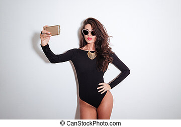 Attractive woman in bodysuit making selfie photo