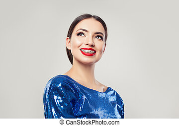 Attractive woman in braces smiling on white background