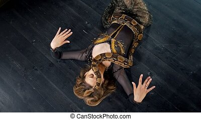 Attractive woman in bright costume dance lying on the floor with a snake