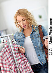 Attractive woman in clothing store checking price