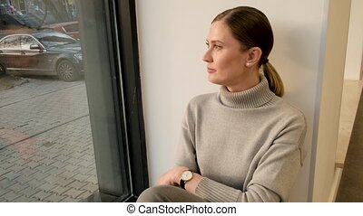 Attractive brunette woman wearing grey cowl neck pullover looks out of window on city street sitting on sill in light office