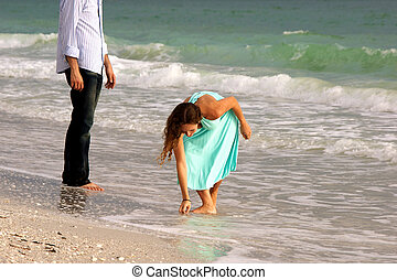 attractive woman in dress stoops to pick up shell on beach