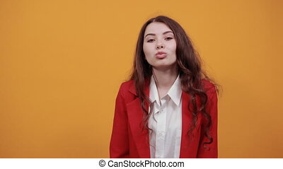 Attractive caucasian young woman in fashion white shirt and red jacket blowing, send air kiss isolated on orange background in studio. People sincere emotions, lifestyle concept.