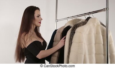 Attractive woman in front of clothing rack with hanging fur jackets