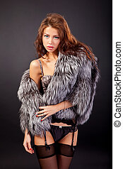 Attractive woman in fur coat and bra. Shot in a studio on a...