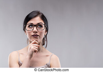 Attractive woman in glasses deep in thought