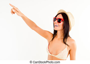 Attractive woman in hat, bikini and spectakles pointing on smth