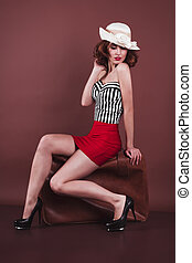 Attractive woman in hat with a suitcase