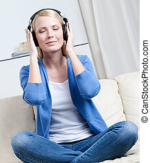 Attractive woman in headphones listens to music