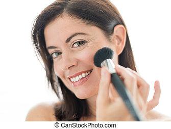 attractive woman in her forties applying makeup - Beautiful...