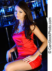 Attractive woman in night club with a drink - Portrait of...