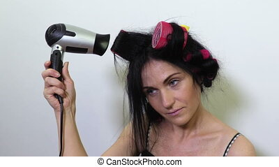 Attractive woman in pajama and hair rollers drying hairs