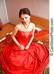 Attractive woman in red dress sitting on the bed