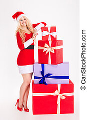 Attractive woman in santa claus dress posing with gift boxes