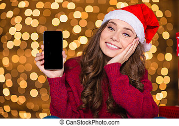 Attractive woman in santa hat holding mobile phone blank screen