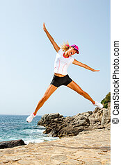 Attractive woman in sportswear jumping outdoors.