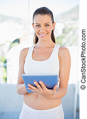 Attractive woman in sportswear using tablet in bright...