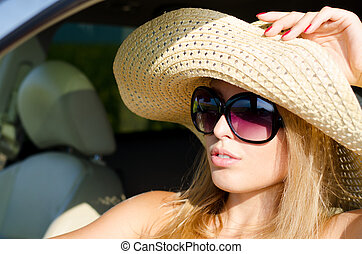 Attractive blonde woman sitting in a car in sunglasses and a wide brimmed straw sunhat