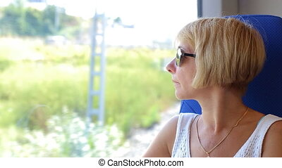 Attractive woman in thought looking out of a train window