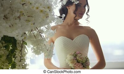 Attractive woman in wedding dress with beautiful bride's bouquet